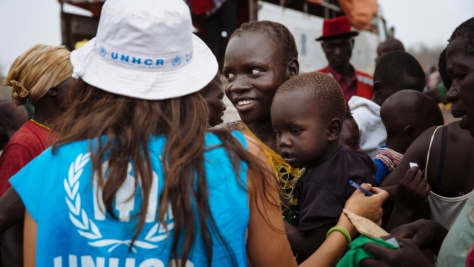 A UNHCR worker with her back to the camera with a group of people, one carrying a young child.