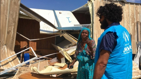 A displaced woman speaks to a man wearing a blue UNHCR vest in front of her collapsed shelter in Triq al Matar settlement in Libya.