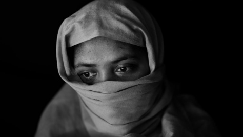 Black-and-white portrait of a 20-year-old Rohingya woman wearing a headscarf.