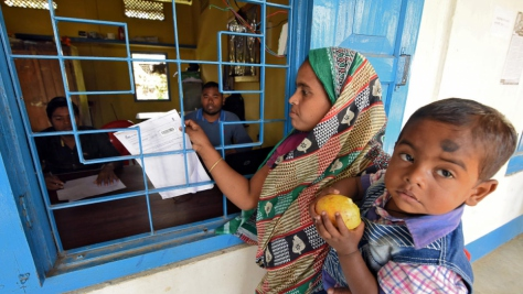 A woman carrying her son arrives to check her name on the draft list of the National Register of Citizens at an NRC centre in Chandamari village, India,