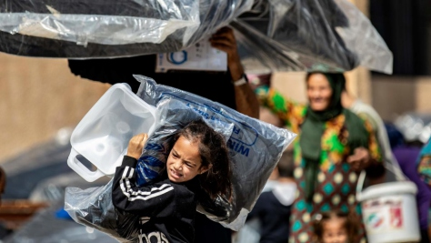 Syria. Young girl displaced by recent violence carries relief supplies