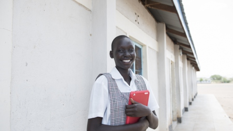 Kenya. Mary standing outside school holding a tablet