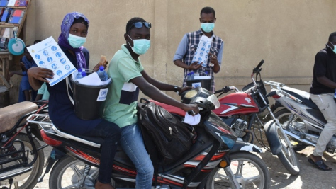 Wearing protective masks, Idriss, 21, and Leila, 25, both refugees from the Central African Republic, travel through N'Djamena, Chad distributing materials to raise awareness about COVID-19.