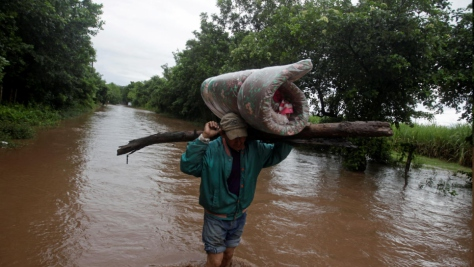 Honduras. Man carries his belongings through a flooded road after the passing of Storm Iota, in Marcovia