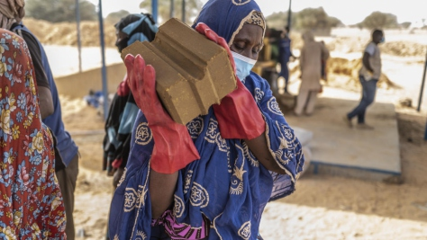 Construction workers representing both the refugee and local communities build the first of 1,000 brick homes to be built in Ouallam village in Niger.
