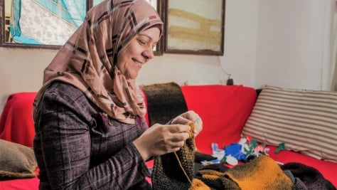 A refugee woman is knitting a colourful, woollen scarf. UNHCR, the UN Refugee Agency - MADE51