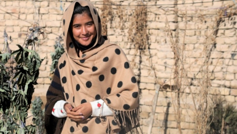 UNHCR, the UN Refugee Agency - Mahbooba, a 22-year-old Afghan refugee woman in Pakistan, stands outside her home, wrapped in a beautiful polka dot scarf.